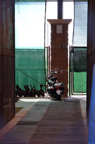 "from the photographer: ""It must be Spring Training. Motorcycle parked in the batting cages at Royals/Rangers Spring Training Stadium"""